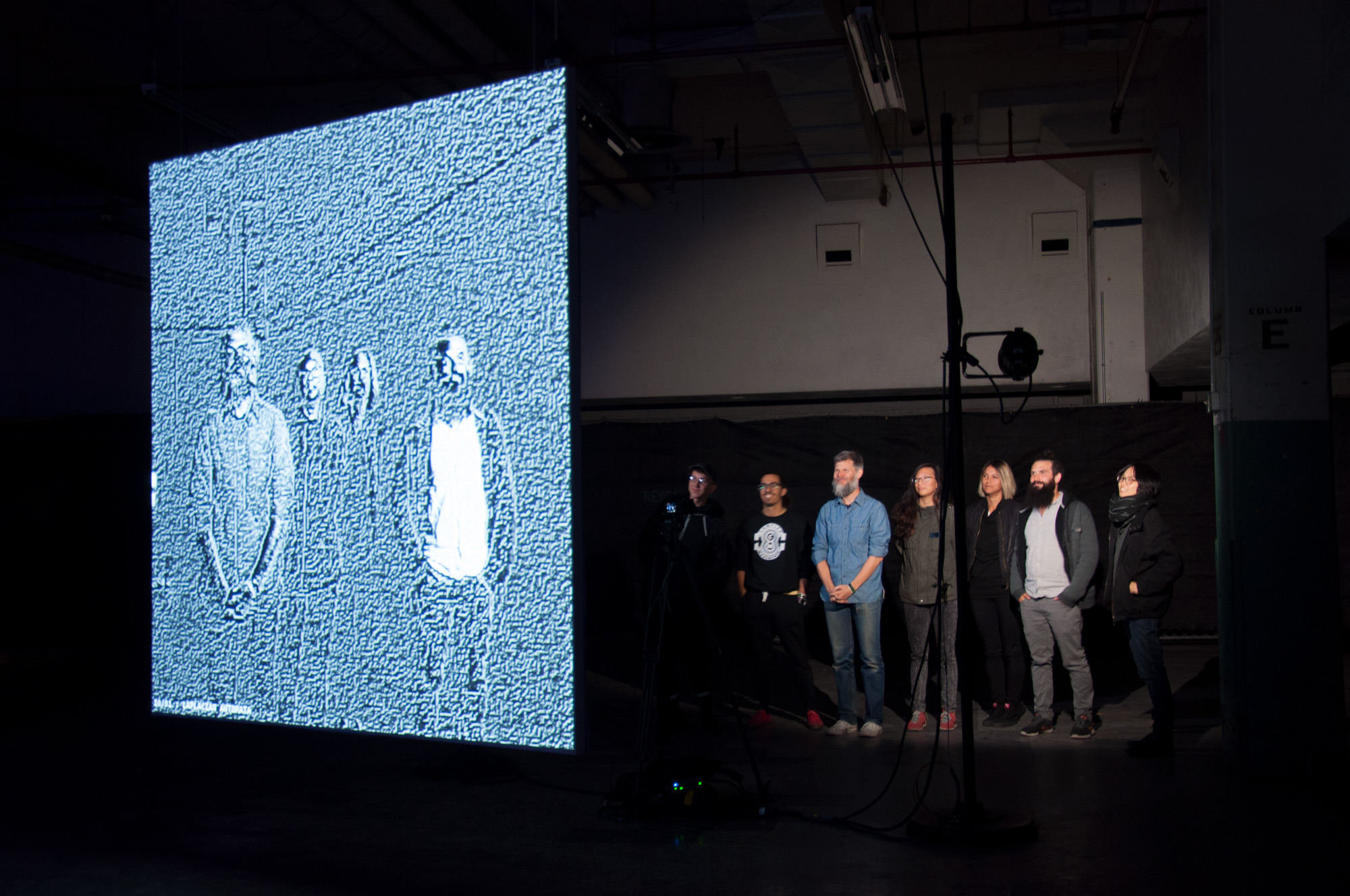 Seven people looking at a filtered projection of themselves on a screen.