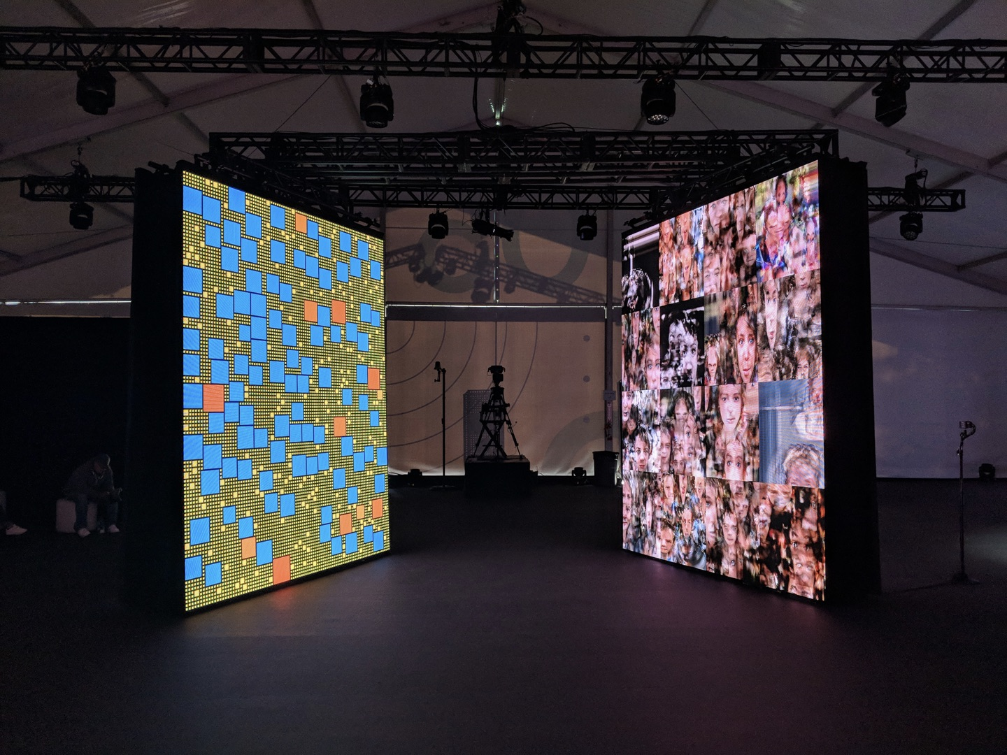 Two large LED screens, one with a colorful block pattern, another with odd faces.