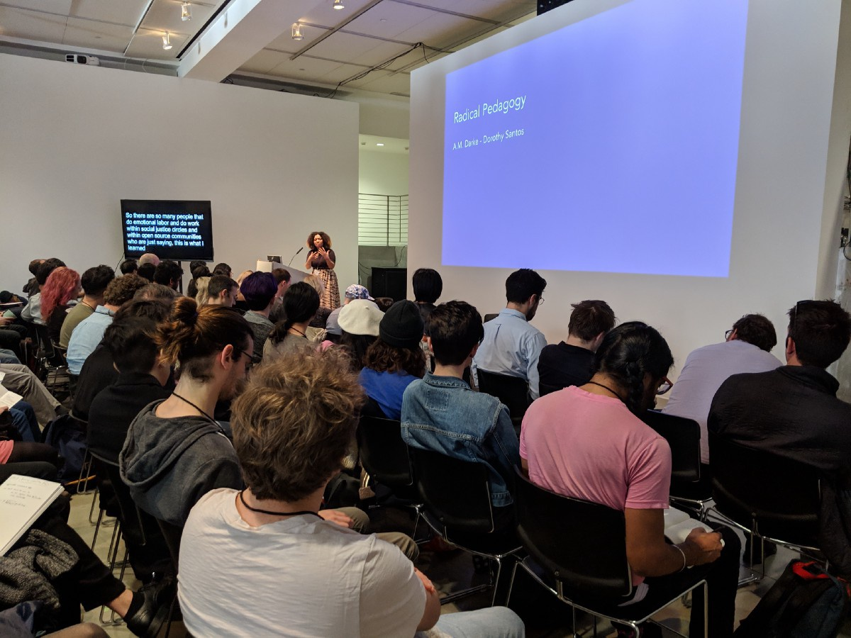 A woman giving a presentation to a full room in front of a screen that reads 'Radical Pedagogy.'
