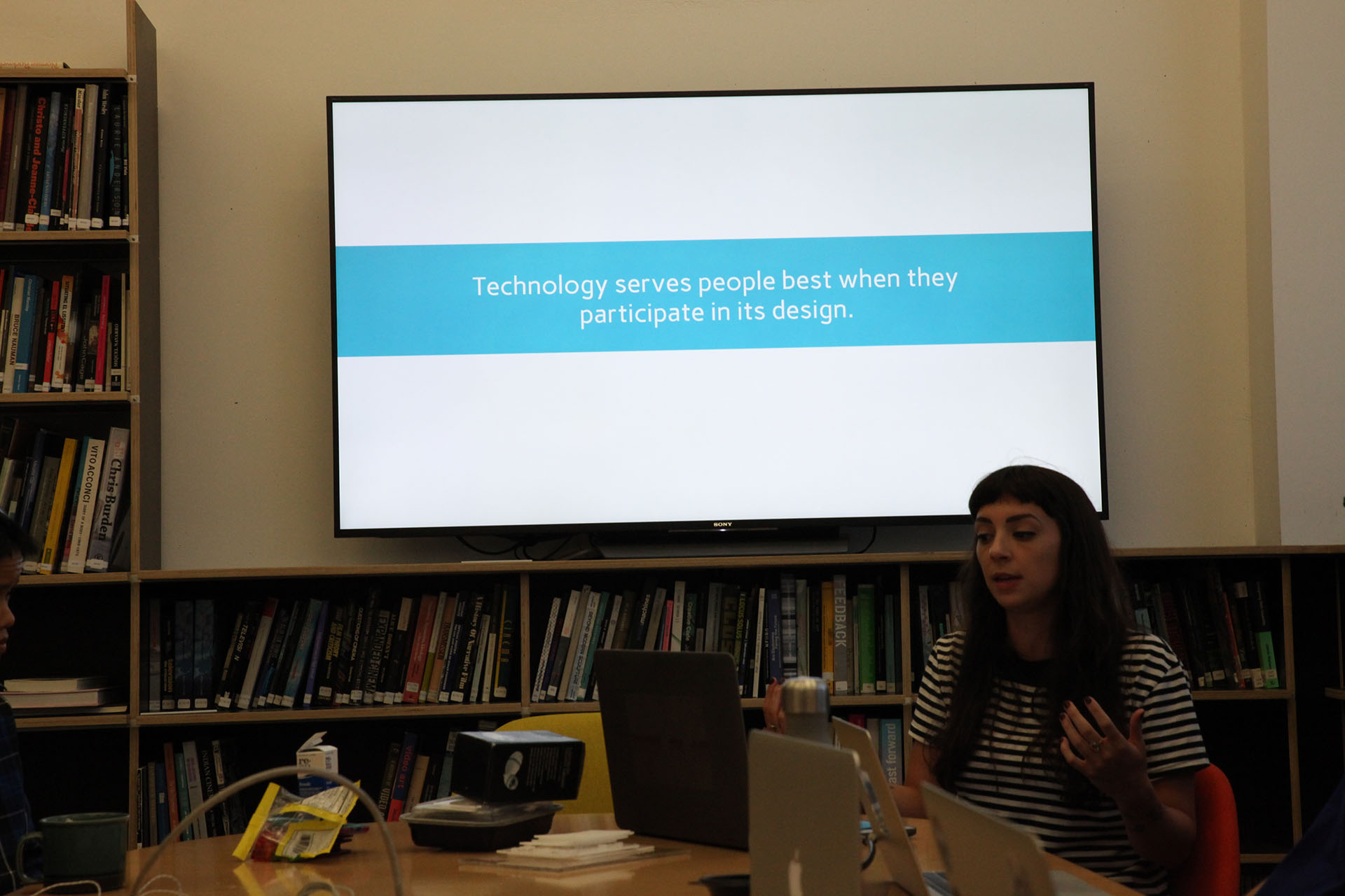 A woman giving a presentation in front of a TV. The presentation on the screen reads 'Technology serves people best when they participate in its design.'